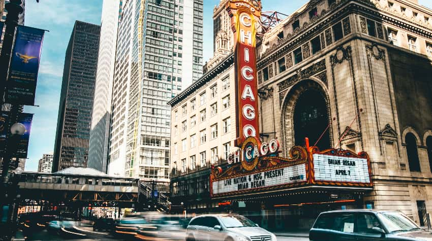 A historic Chicago theatre surrounded by passing cars