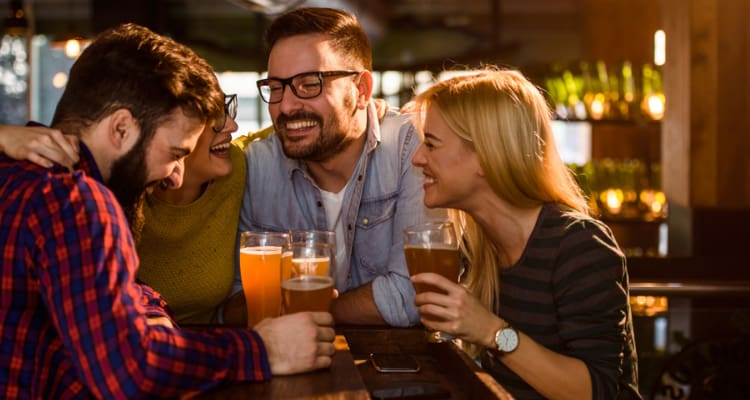 friends smile and hold their beer glasses at a brewery