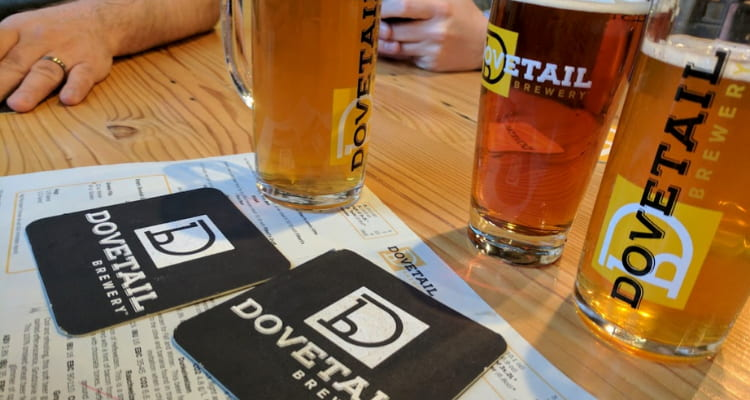 """drink glasses filled with beer and two coasters with """"dovetail brewery"""" logo on them"""
