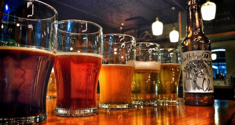 a row of glasses with different colored beers in them