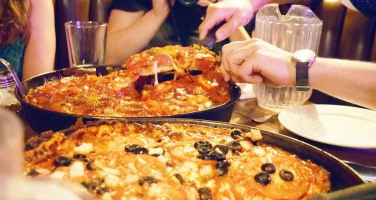 People cutting a slice of Chicago deep dish pizza