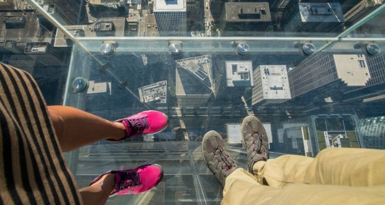 Two people looking down at their feet and Chicago streets from the Skydeck at Willis Tower